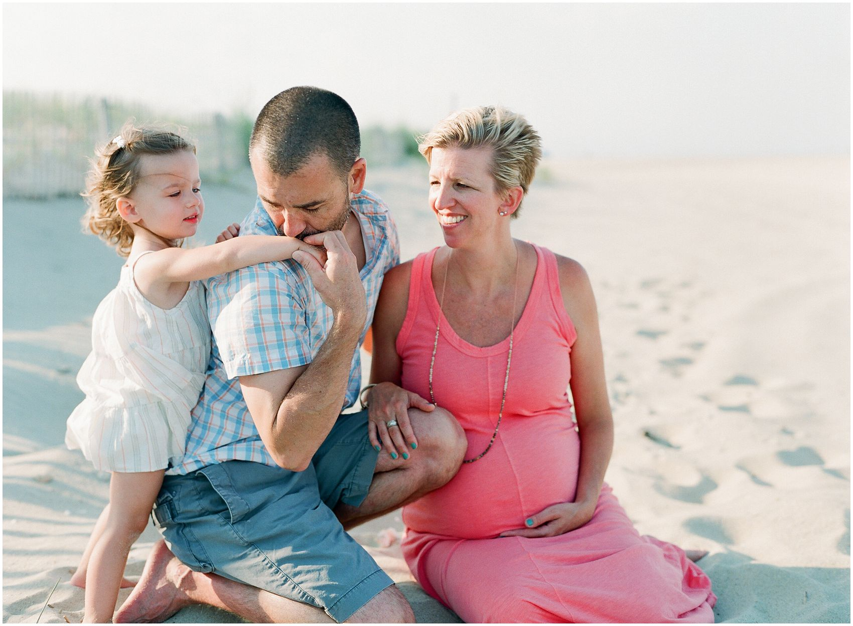 dad kissing his daughter at the beach and pregnant mom looking adoringly at them
