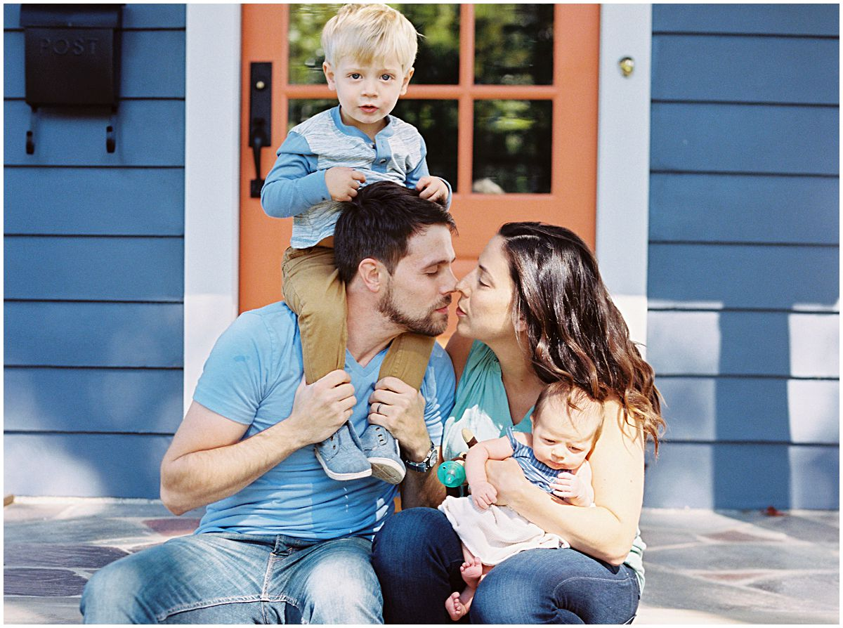 mom and dad want to kiss while holding their kids in front of their home in Montclair NJ.