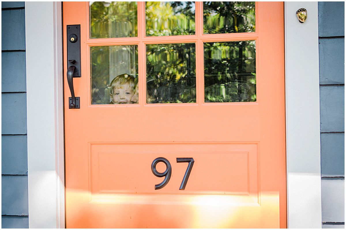 mom and son are peeking from the window of their orange front door in Montclair NJ