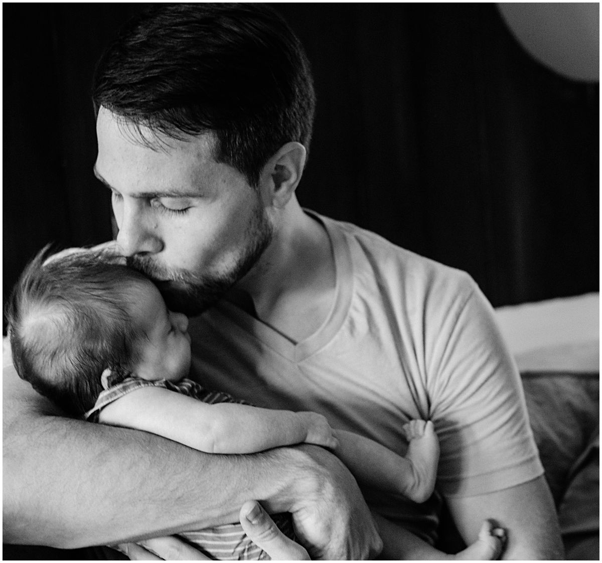 a father tenderly kissing his baby girl in newborn portrait by the best newborn photographer in NYC