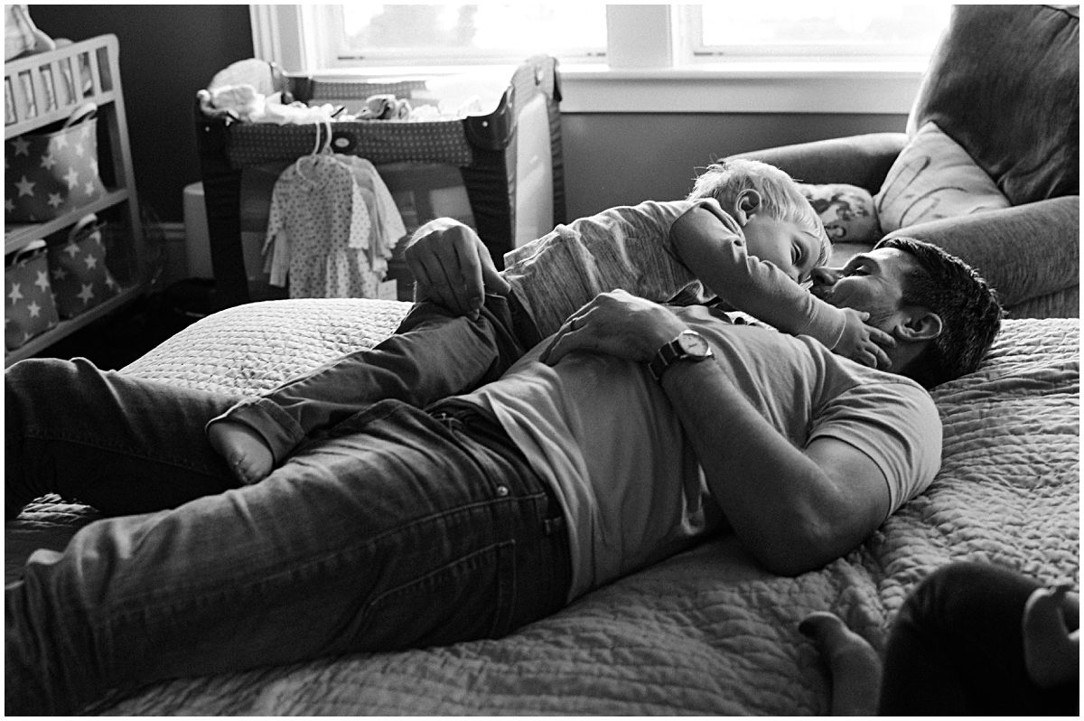 father and son are snuggling in bed in black and white portrait in Essex County NJ