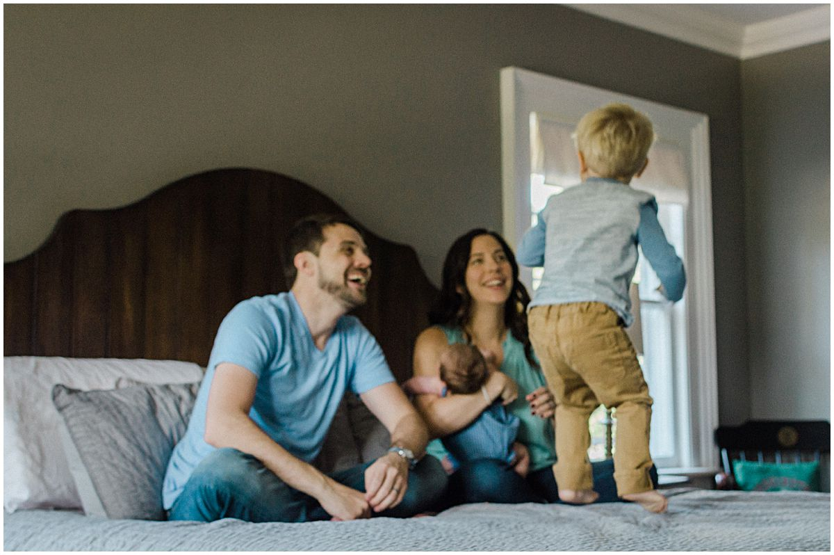 little boy jumping on a big bed as his parents laugh and adore him in Essex County NJ