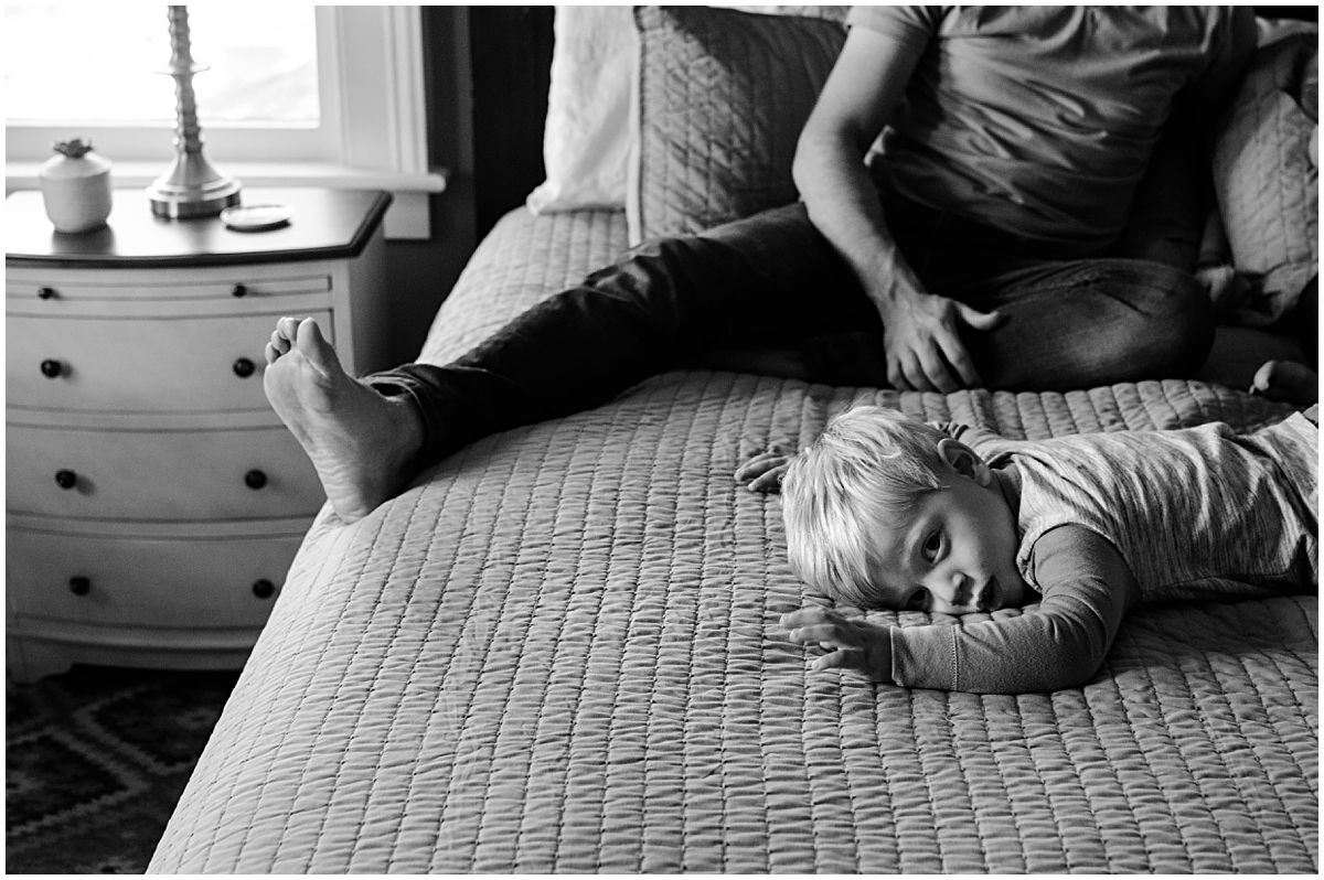 little boy laying on bed in front of his dad in black and white portrait