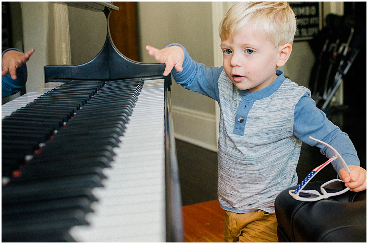 little blond boy playing piano at his home during family photo session in NJ