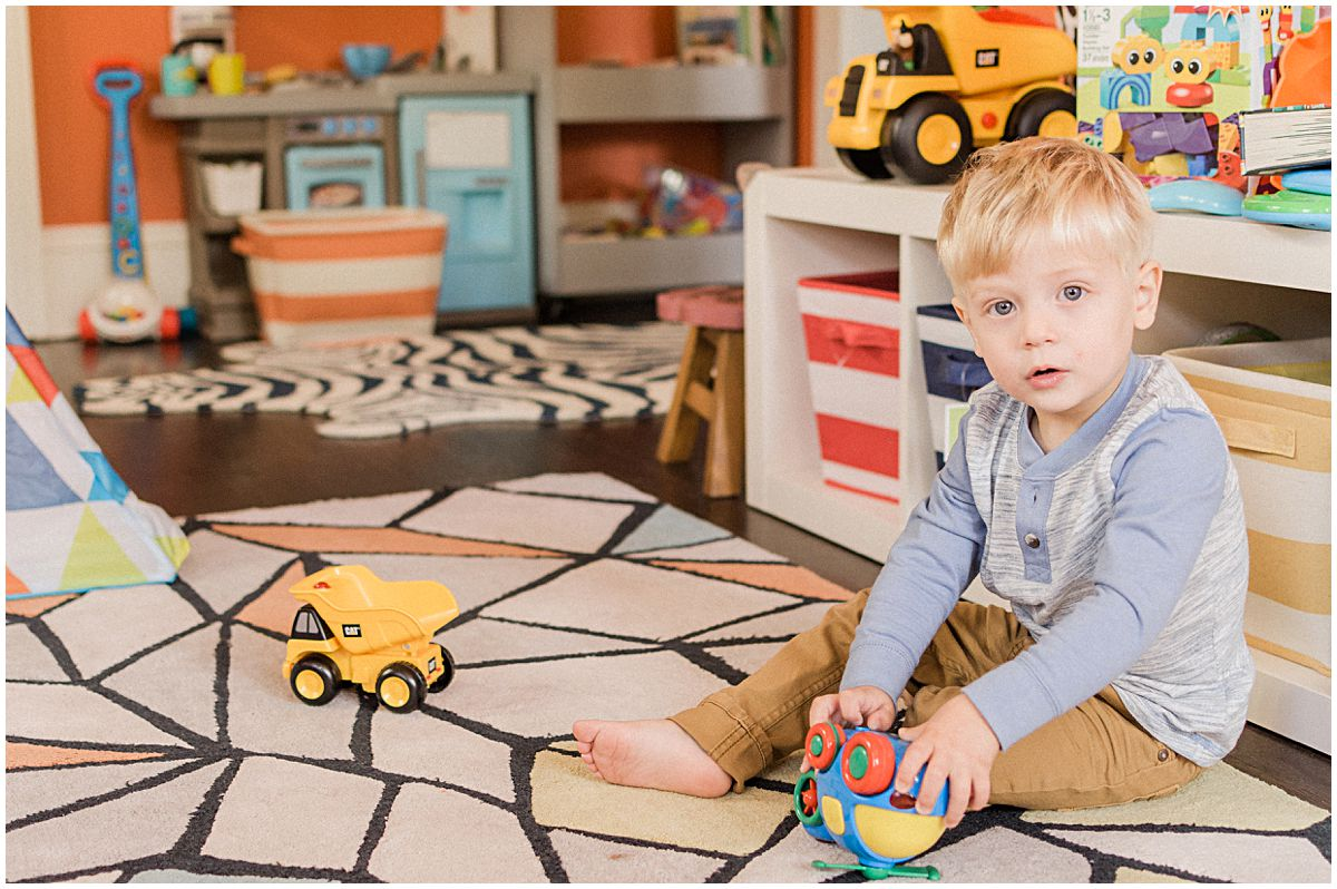 little boy playing with his yellow toy car in the decorative nursery room