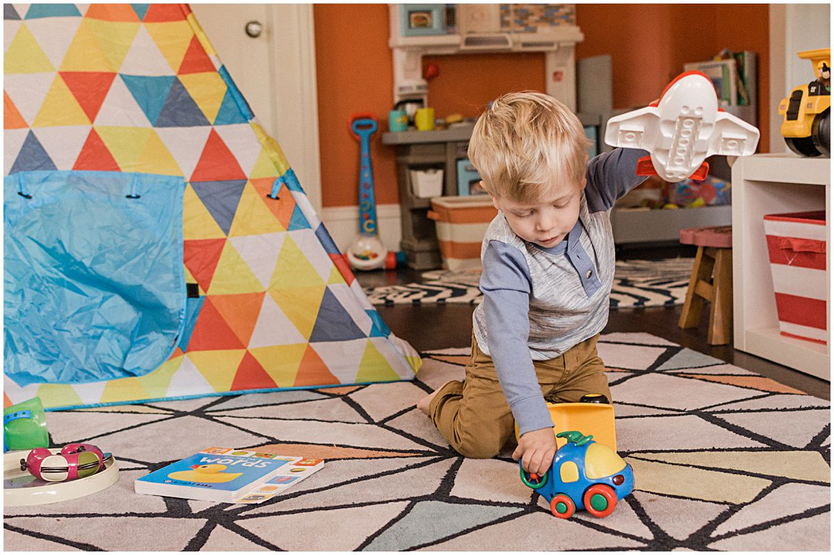 little boy playing airplane in his decorative kids room