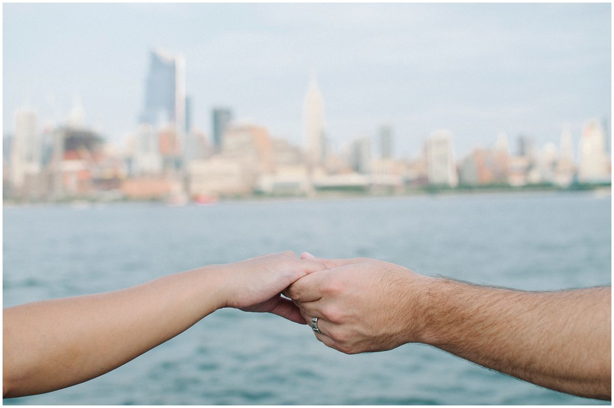 mom and dad hold hands in a family portrait by NYC Skyline