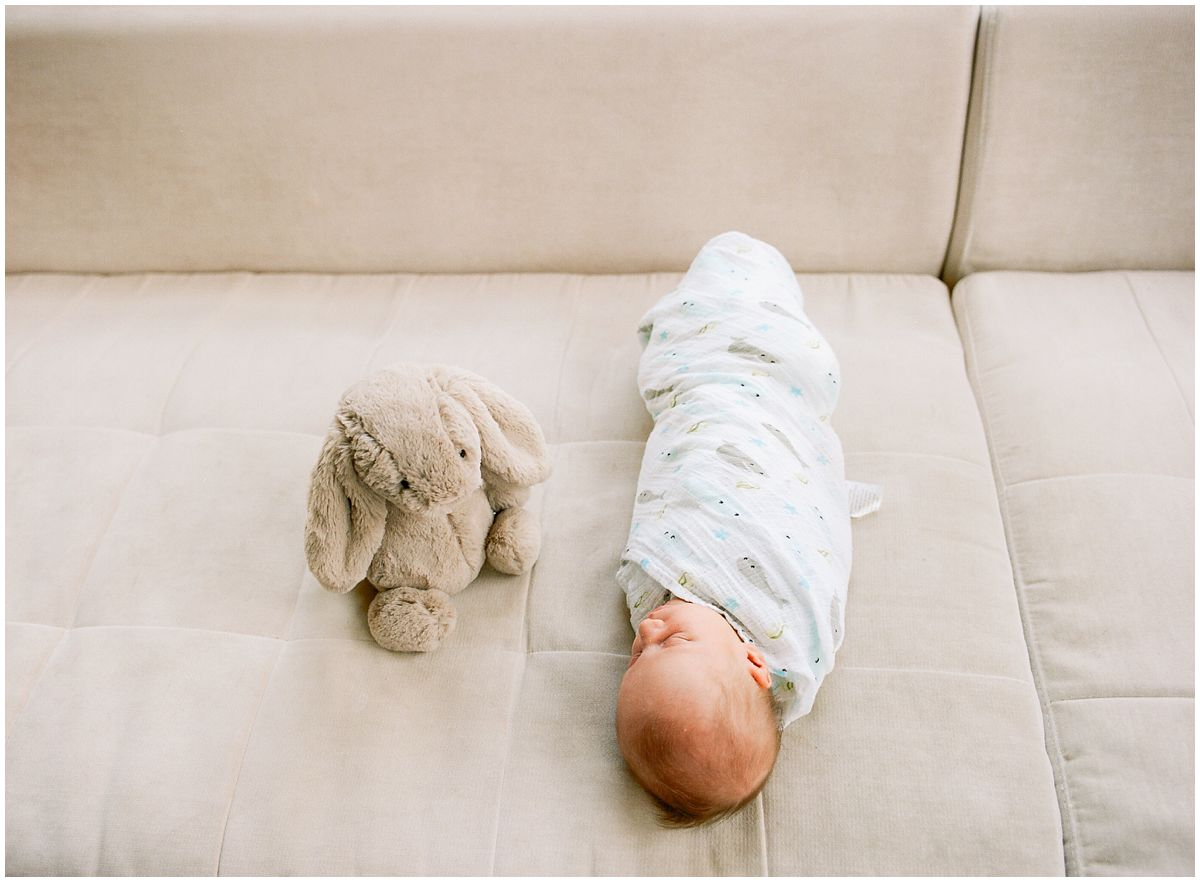 baby boy swaddled in blanket is sleeping on the couch with his toy grey bunny in Hoboken NJ