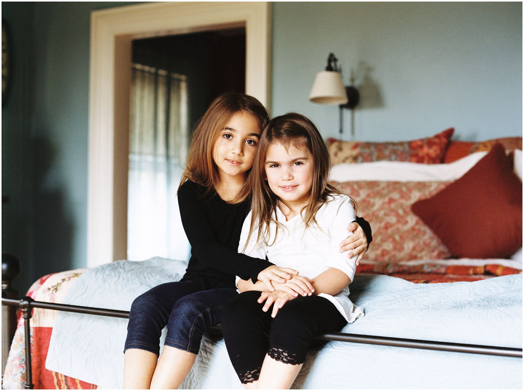 Lifestyle Family Photography with two cute sisters sitting on a bed of their Maplewood NJ home