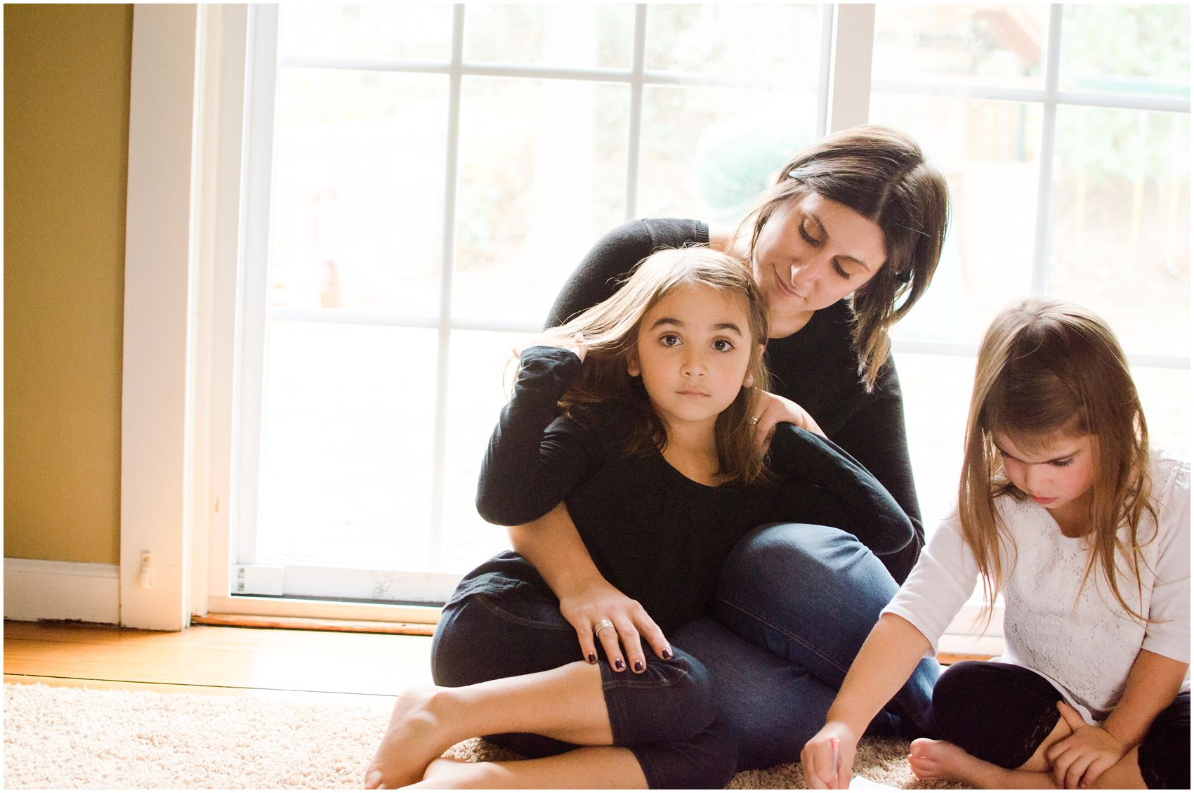Motherhood and Family Photography with mother and two daughters snuggling together in Tenafly , NJ home