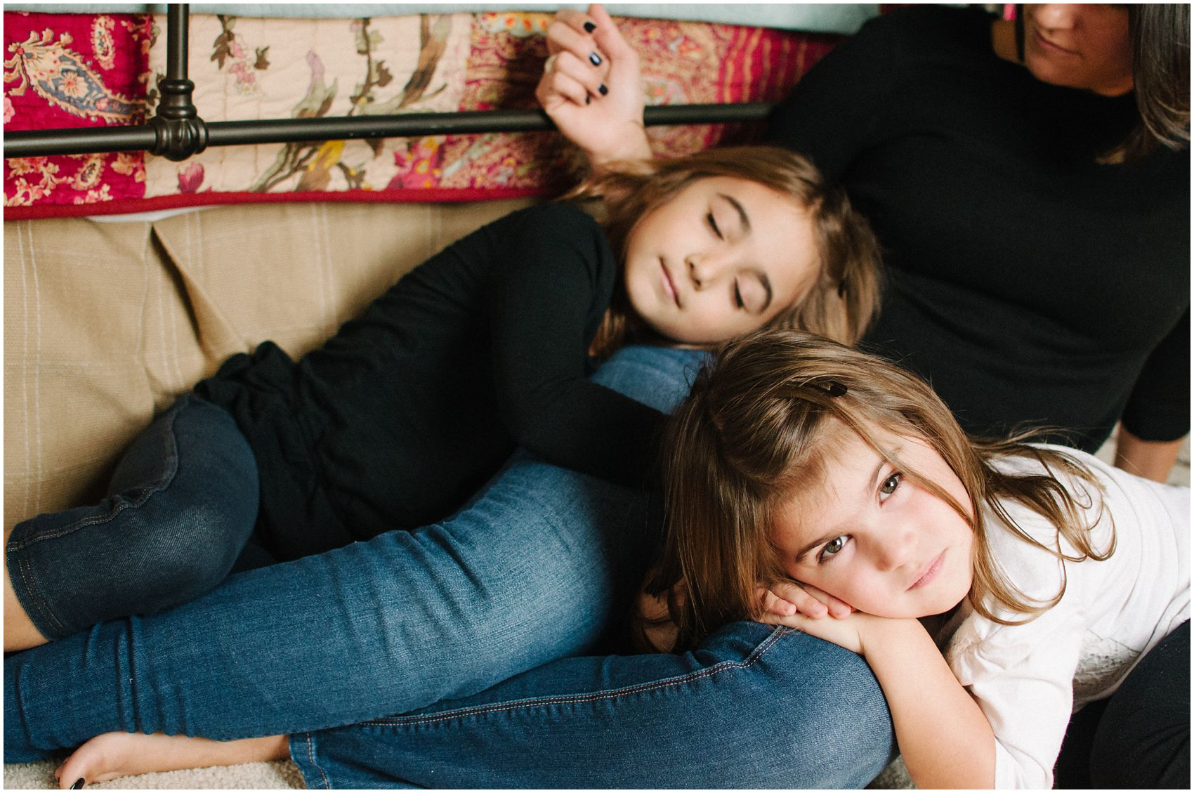 two brunette daughters with long hair are laying on mom during motherhood and family photos
