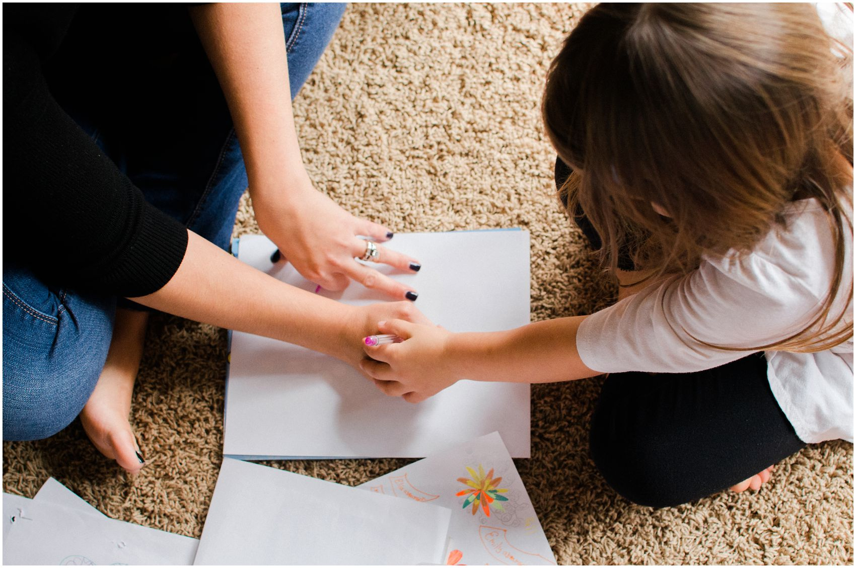 mom and daughter holding hands and coloring a paper on the floor with a pink marker