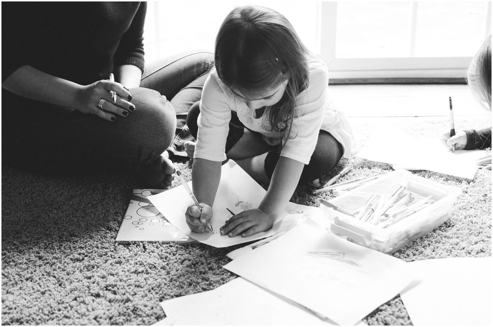 little girl coloring a paper on the floor next to her mom in Bergen County, NJ home