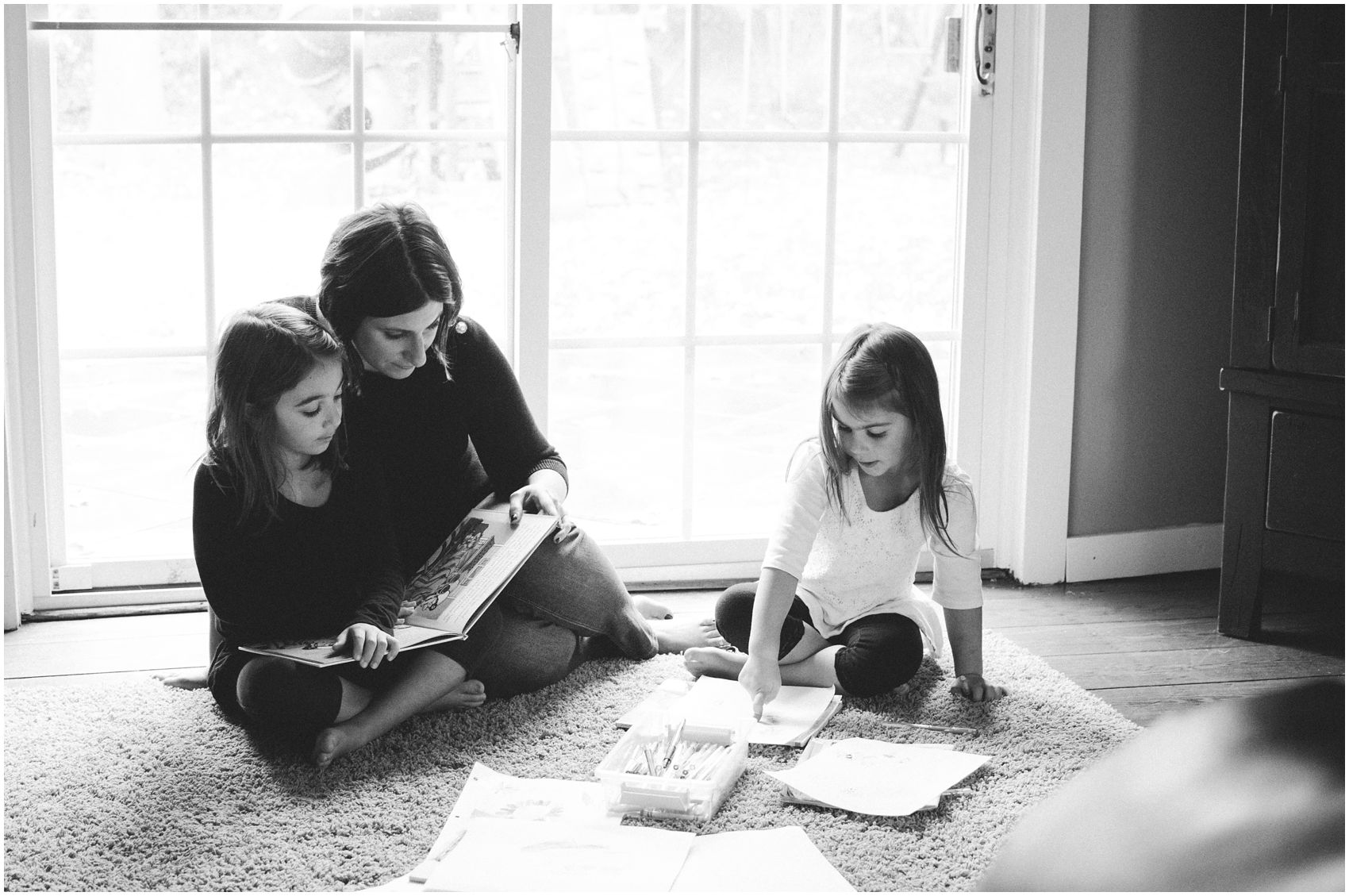A black and white portrait of Mom reading books and coloring with her two preteen daughters in Maplewood Nj