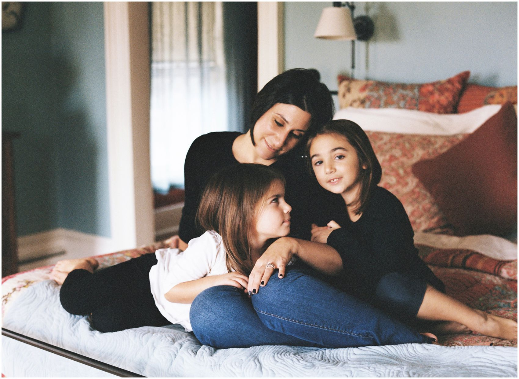 Mother and daughters snuggle together on their bed for a motherhood and family photography portrait in Tenafly, NJ