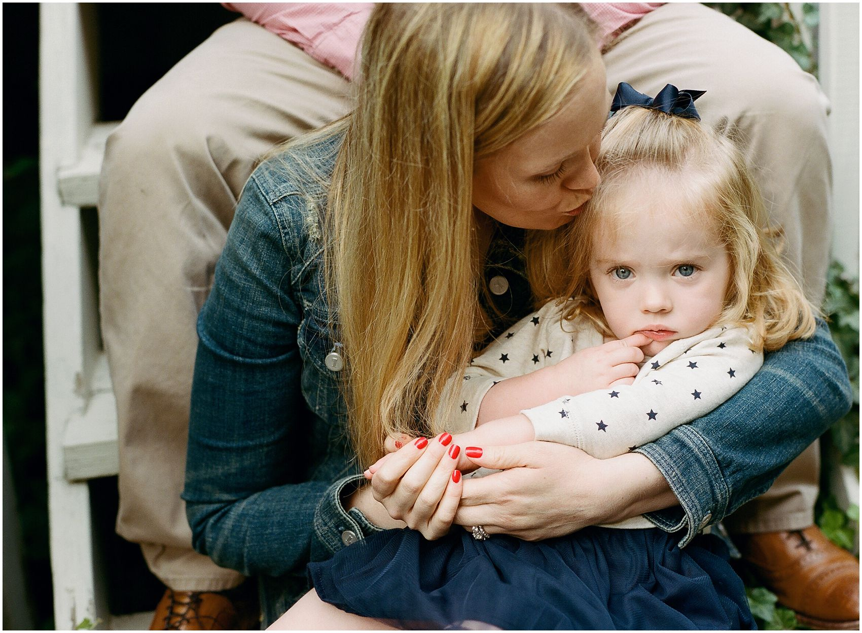 mom kissing little girl with pouty lips in a family portrait