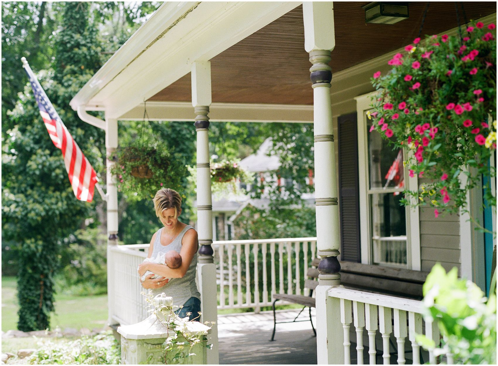 mom holding baby during newborn photo session outside by american flag