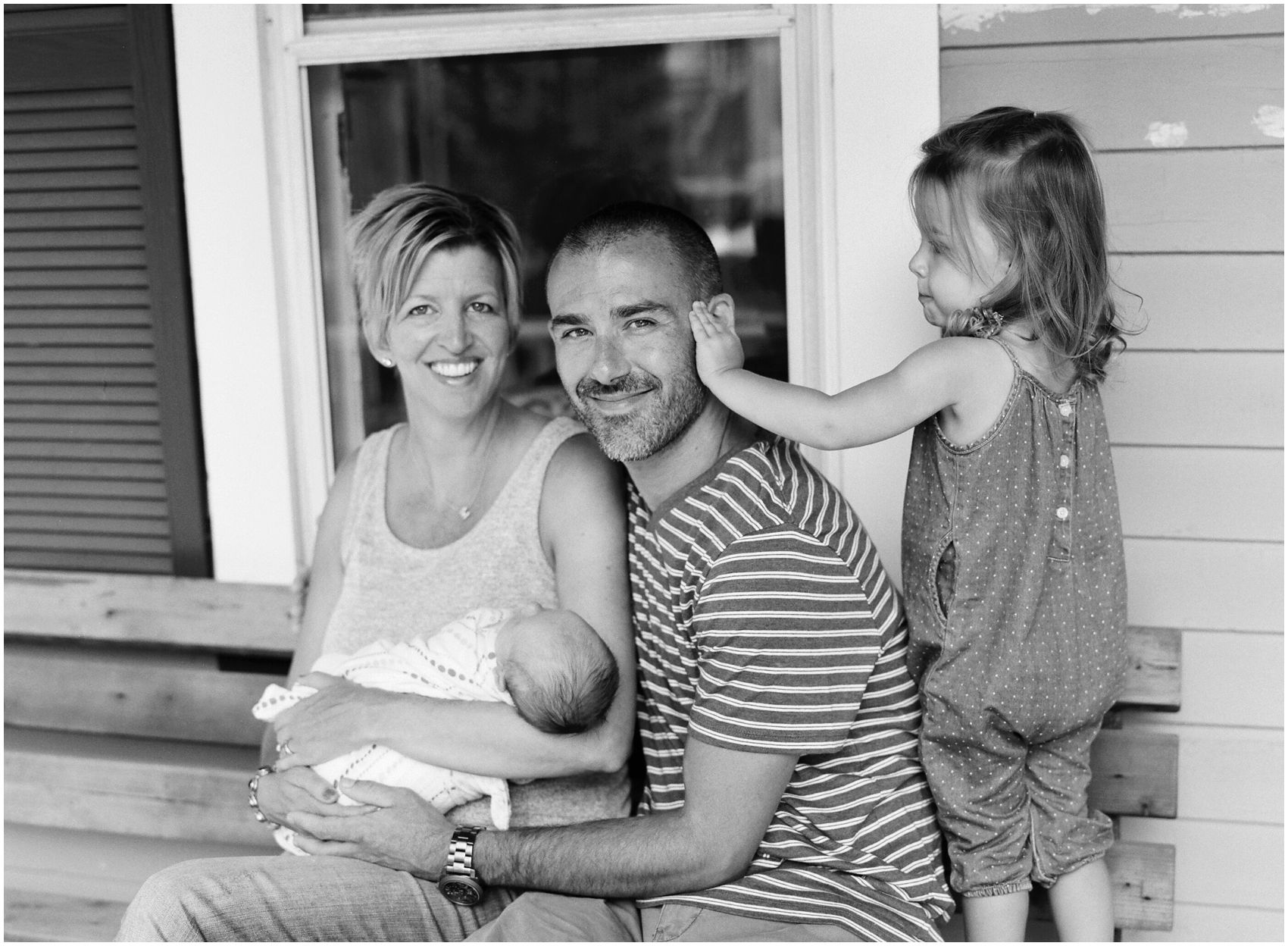 beautiful portrait of family outside their home with two kids
