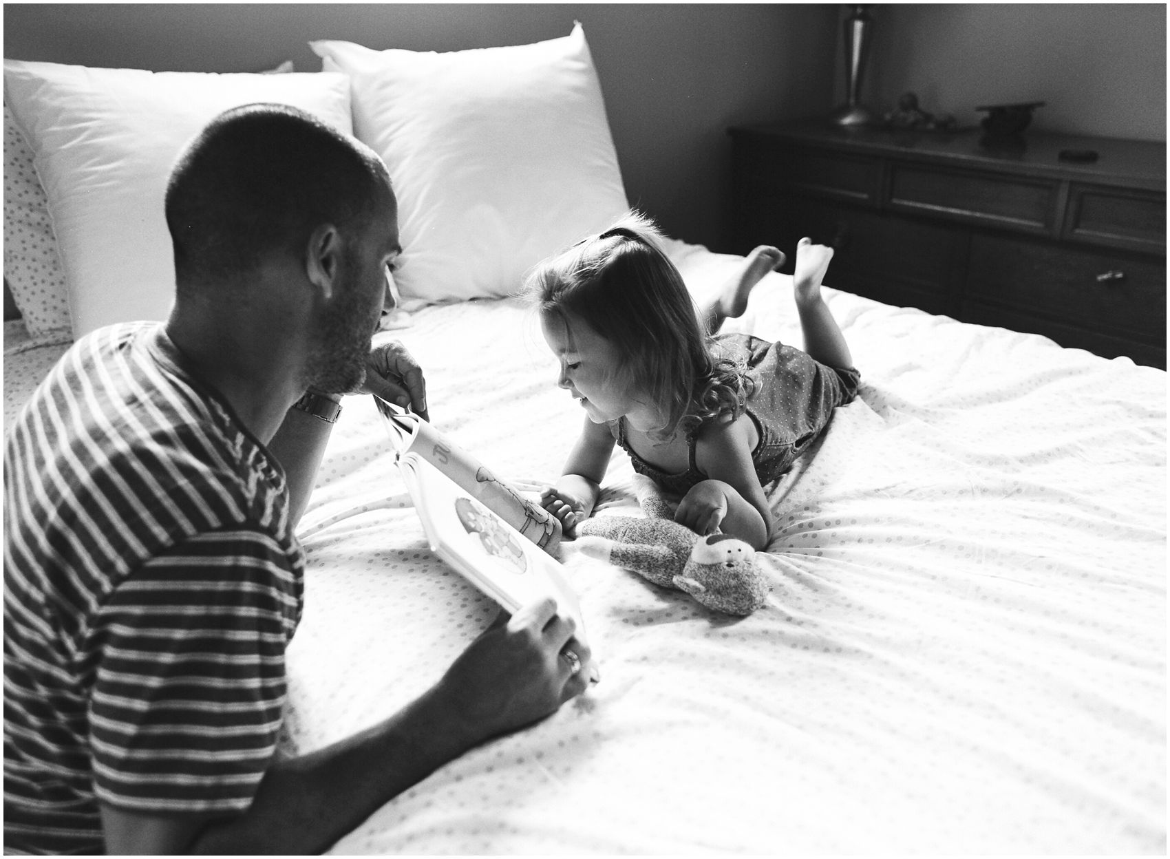 black and white portrait of a dad reading to his daughter