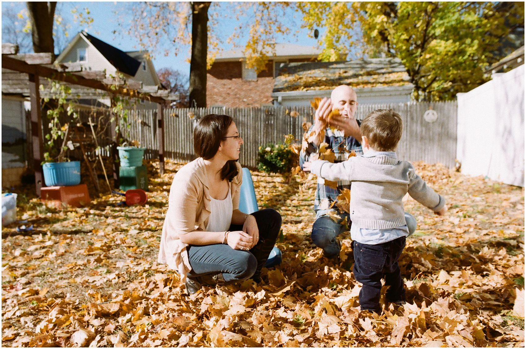 fun family photo of parents playing with yellow leaves with their son during fall season in their NY backyard