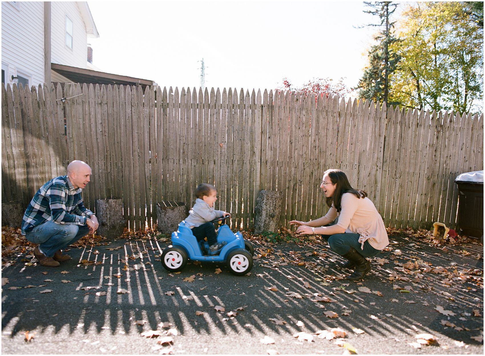fun family photo of a little boy riding a blue car from mom to dad in front of the fence in NY