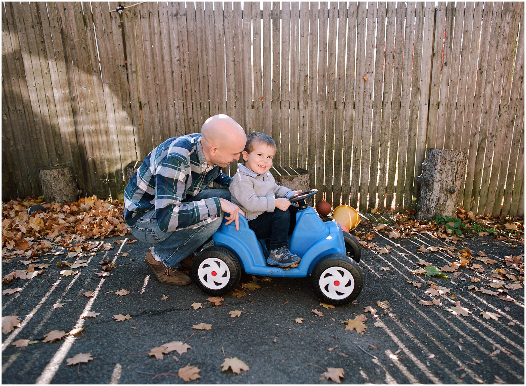 dad pushing his little boy in a blue car surrounded by fall yellow leaves in Rockland County