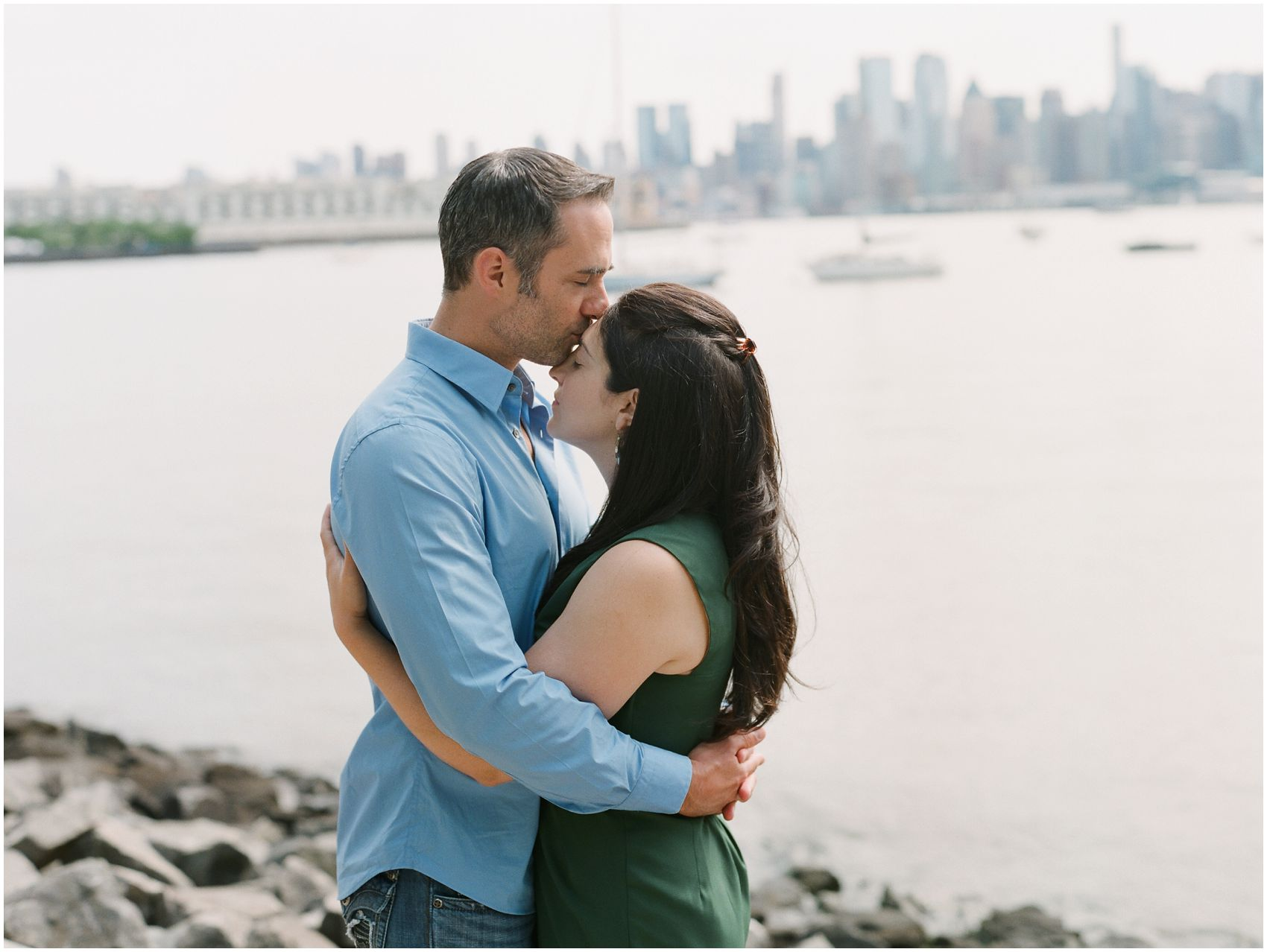 intimate moment of wife and husband embracing each other by the Hudson River in Hoboken NJ
