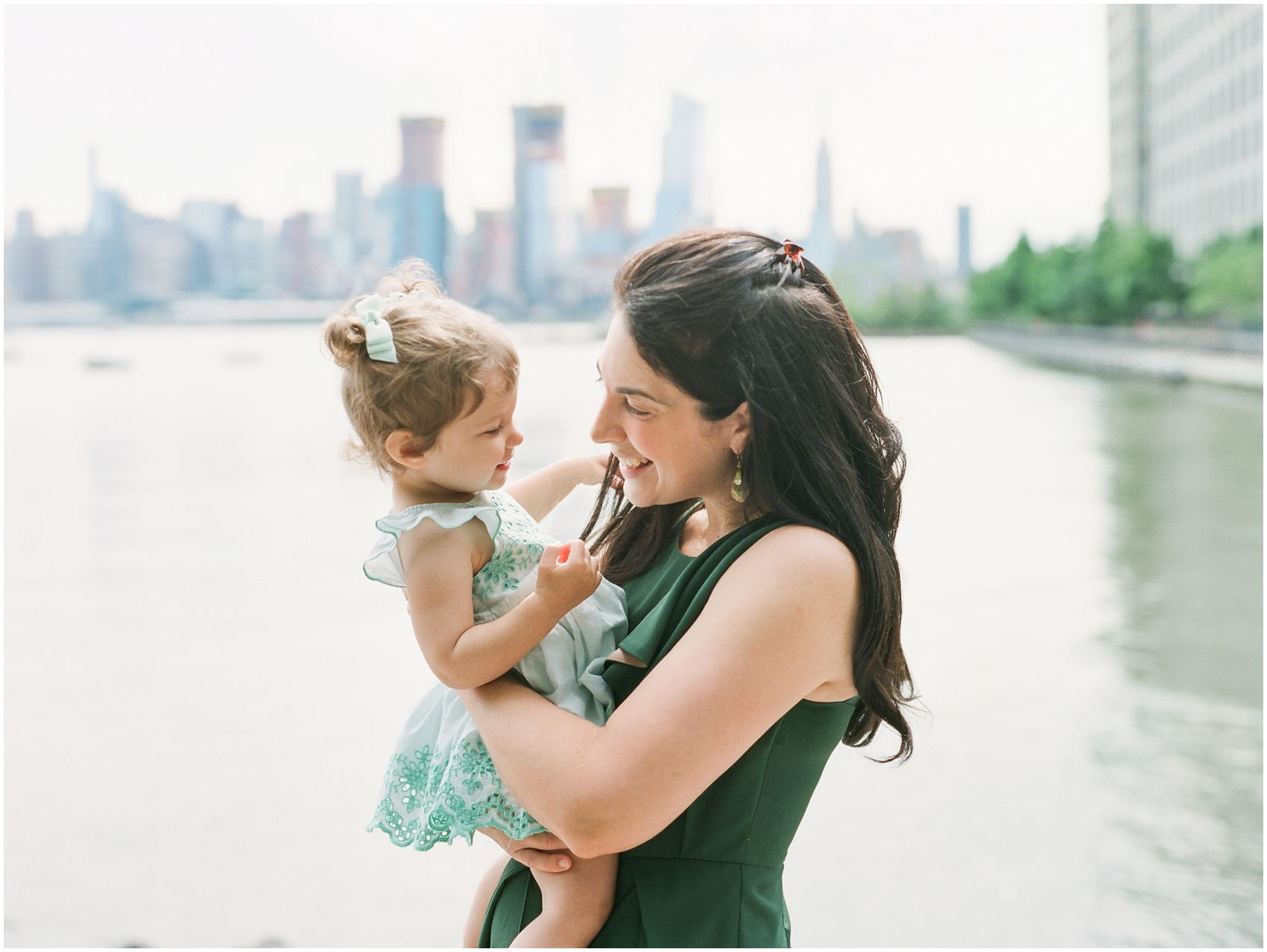 a sweet moment with mom  holding her baby girl and playing with hair by the Hudson River