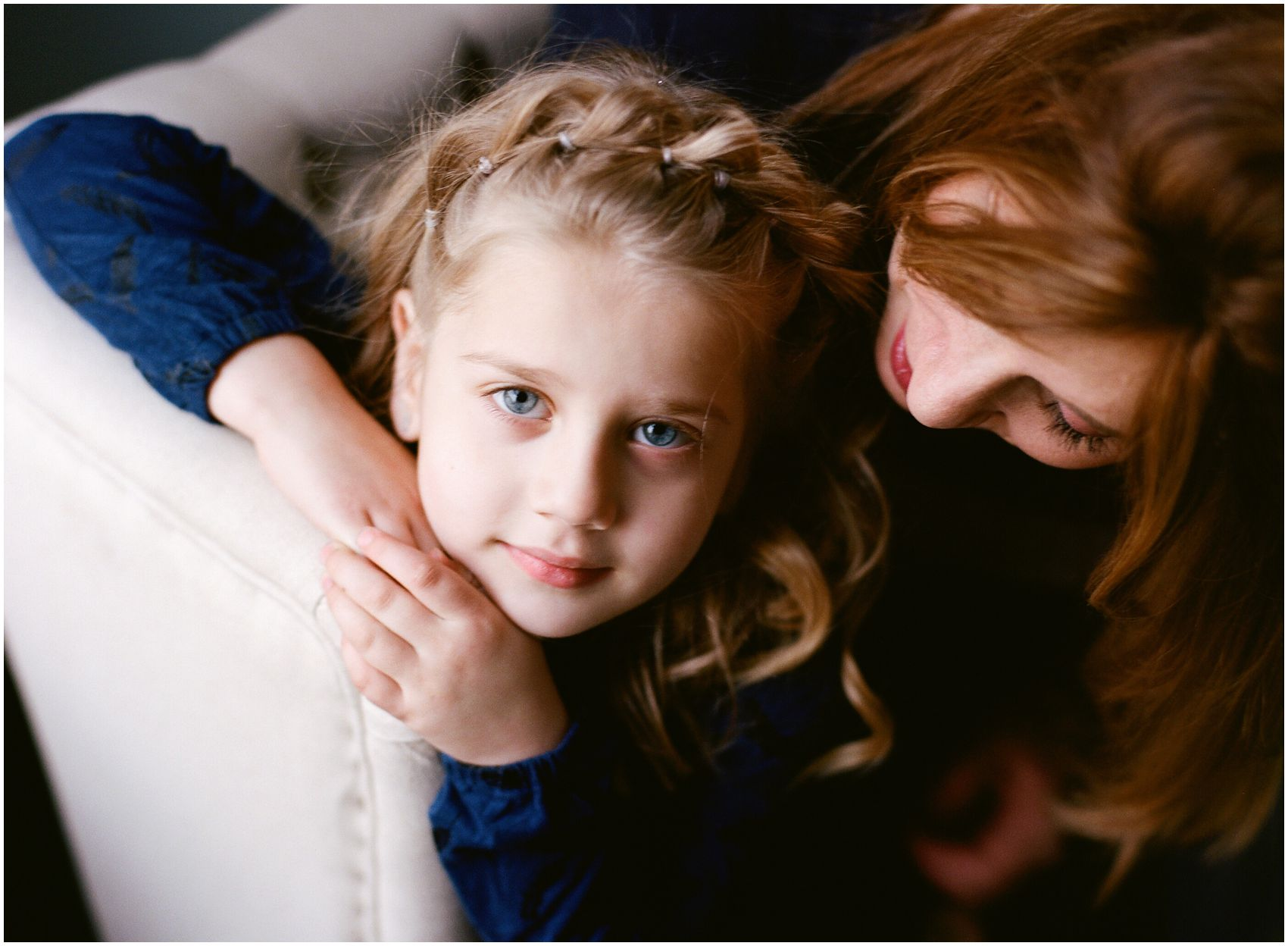 blond girl with blue eyes sitting with her mom