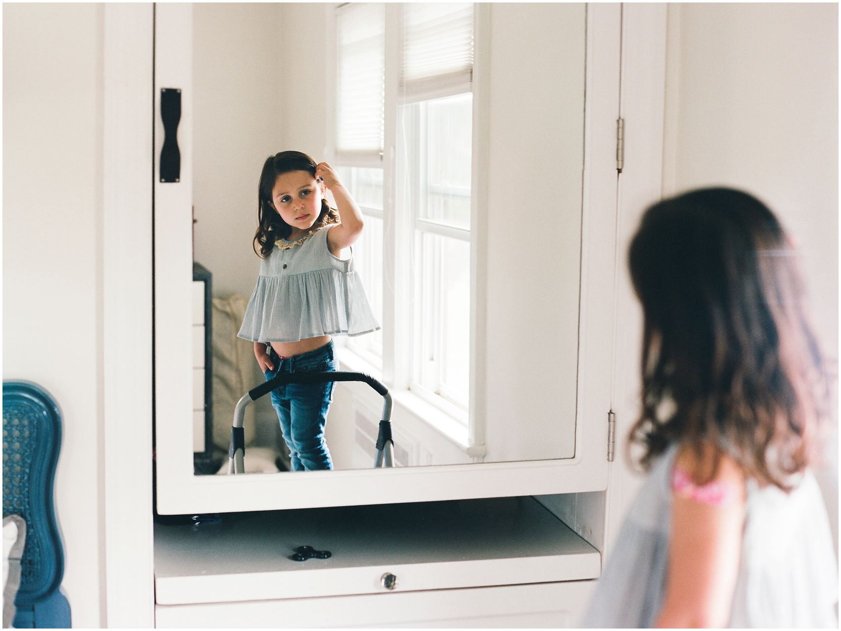 little girl checking herself in the mirror at home for family portraits