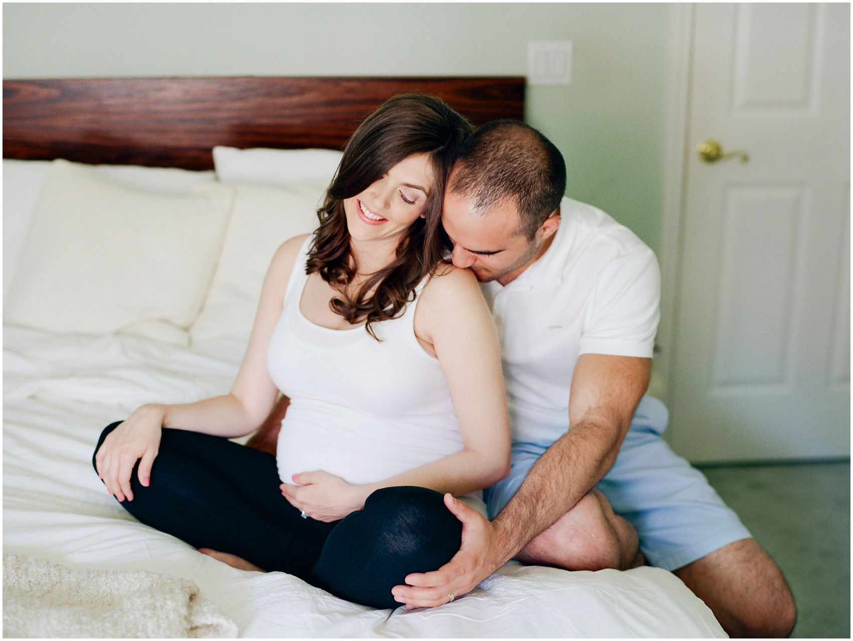 NYC husband kissing his pregnant wife sitting on the white bed wearing tank top and leggings