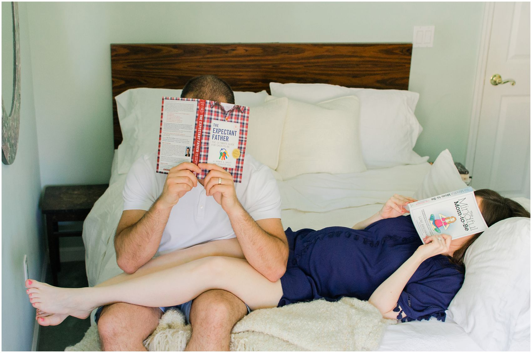 a pregnant couple reading books in bed