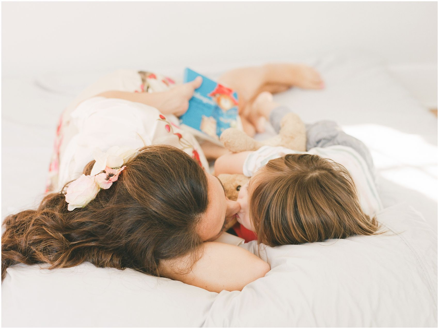 mommy and son giving kisses in bed captured by NYC Family Photographer