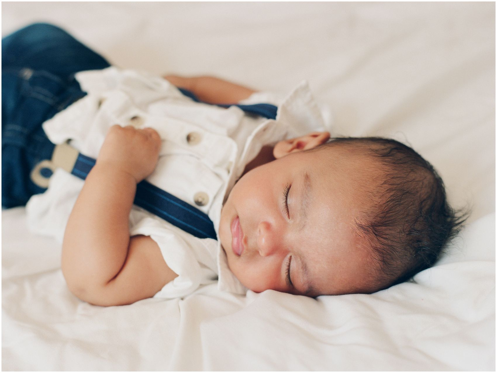 Newborn portrait of a baby boy is sleeping on white bed in NYC