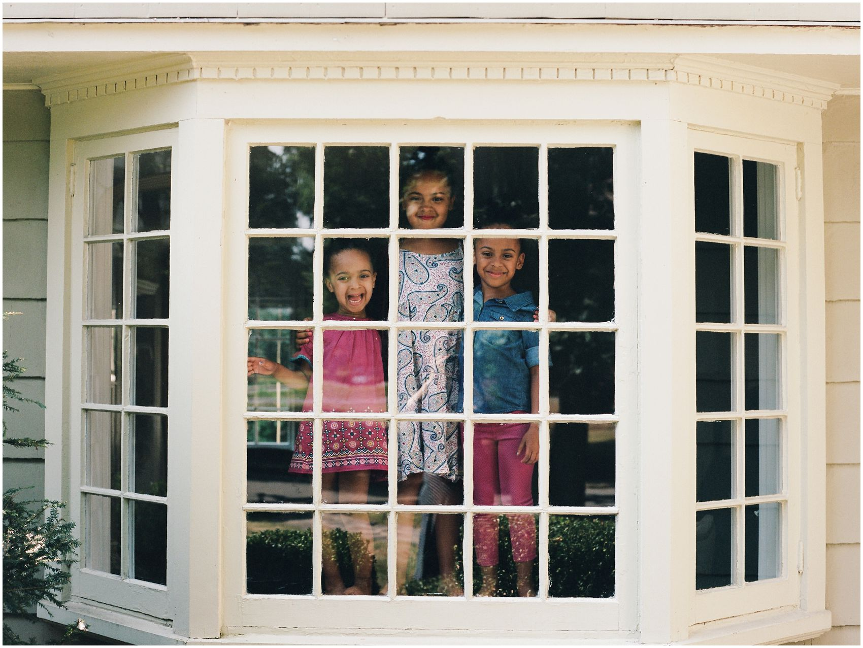 girls looking out in the window of their New Jersey home