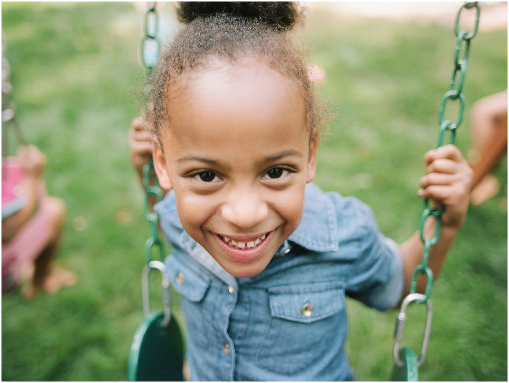 smiling and laughing girl on a swing in her Upper Montclair NJ backyard
