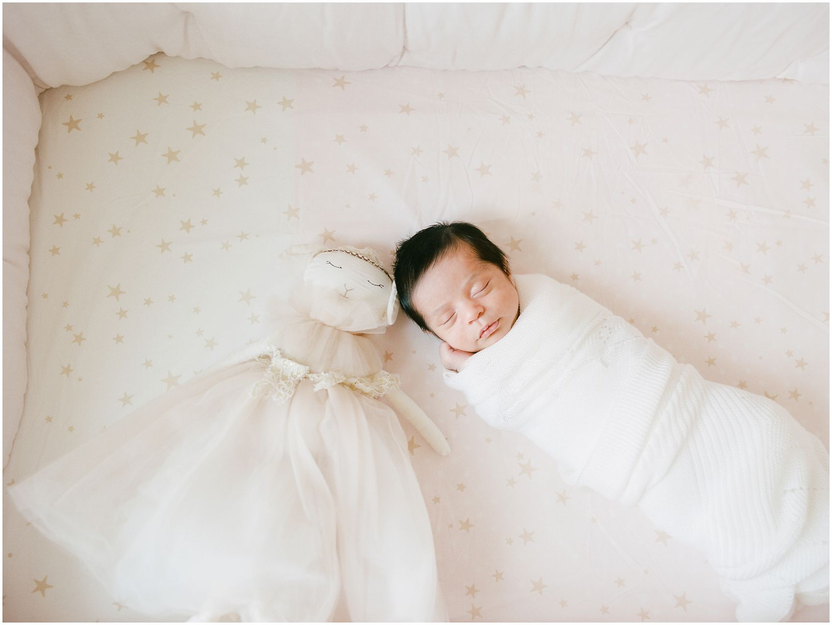 Newborn photographer Miriam Dubinsky shares indoor portraits in tight spaces with a baby girl is sleeping with her doll ballerina