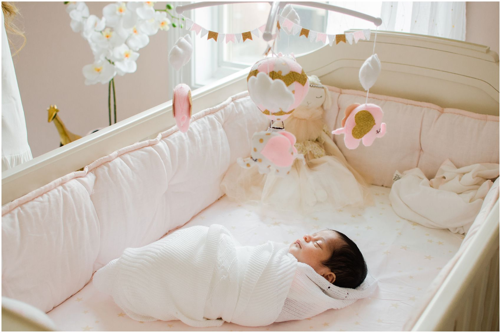 baby girl soundly asleep in the beautifully decorated nursery during her newborn photos in NYC