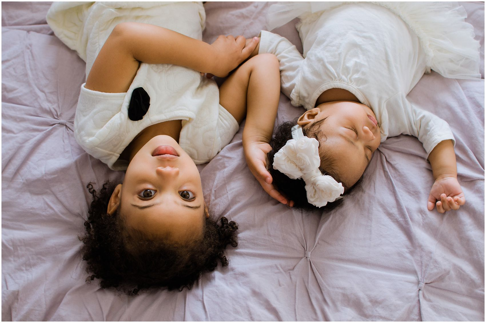 older sister laying down with baby sister for newborn photos