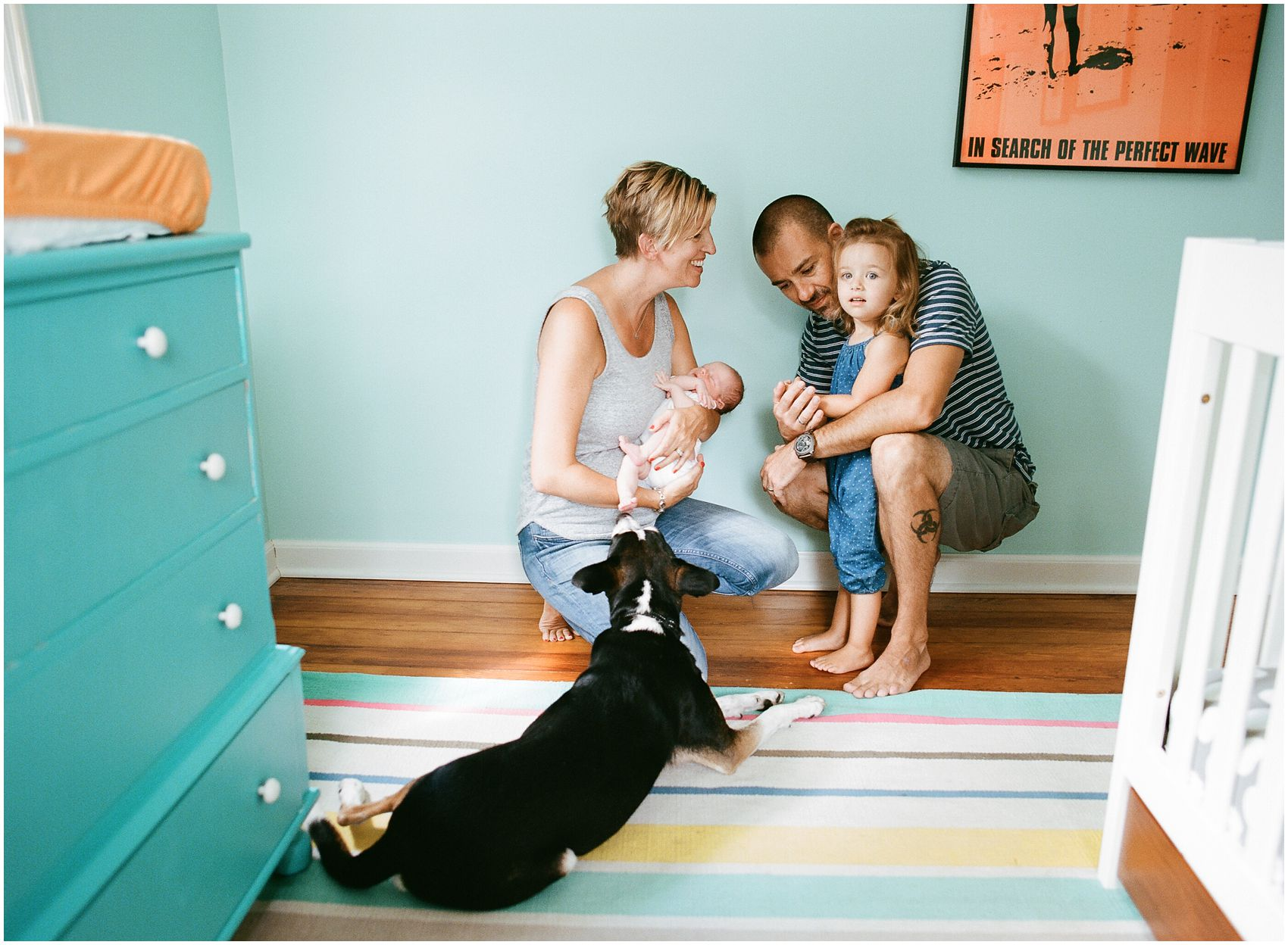mom and dad with two girls and family dog in a decorated nursery