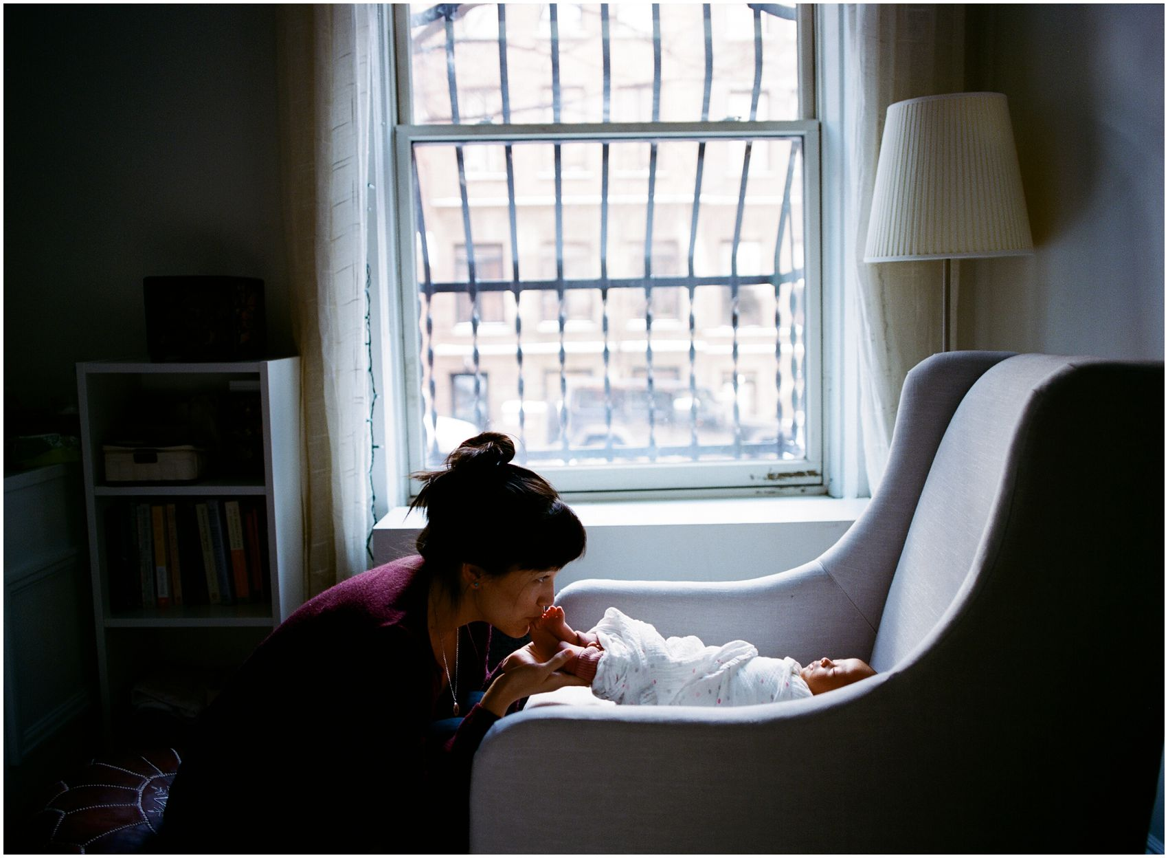 mom kissing her baby's toes by the window