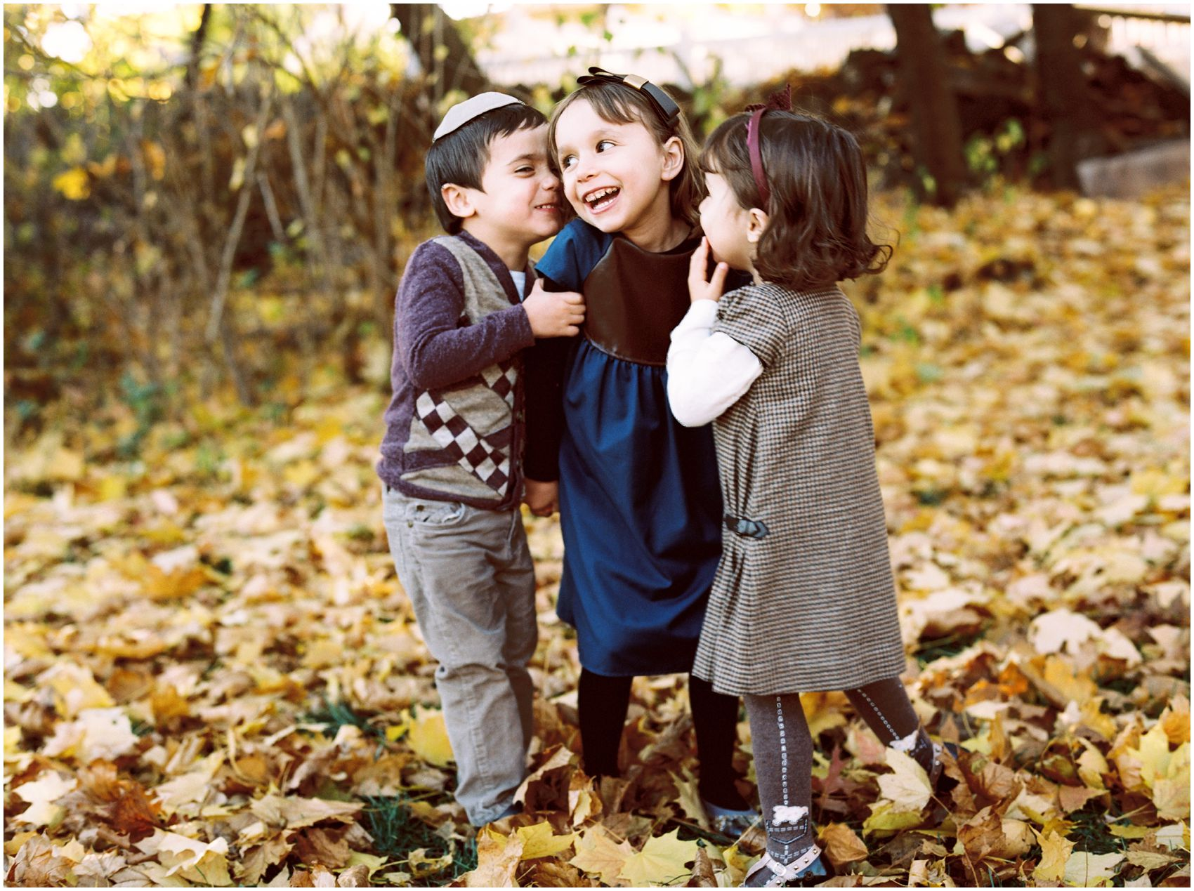 giggling siblings in the park during fall photos