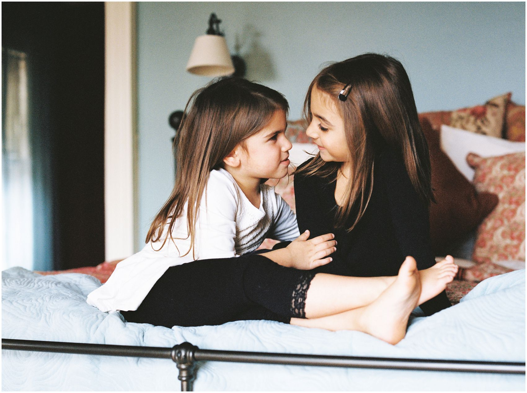 family photos of two sisters sitting lovingly on bed