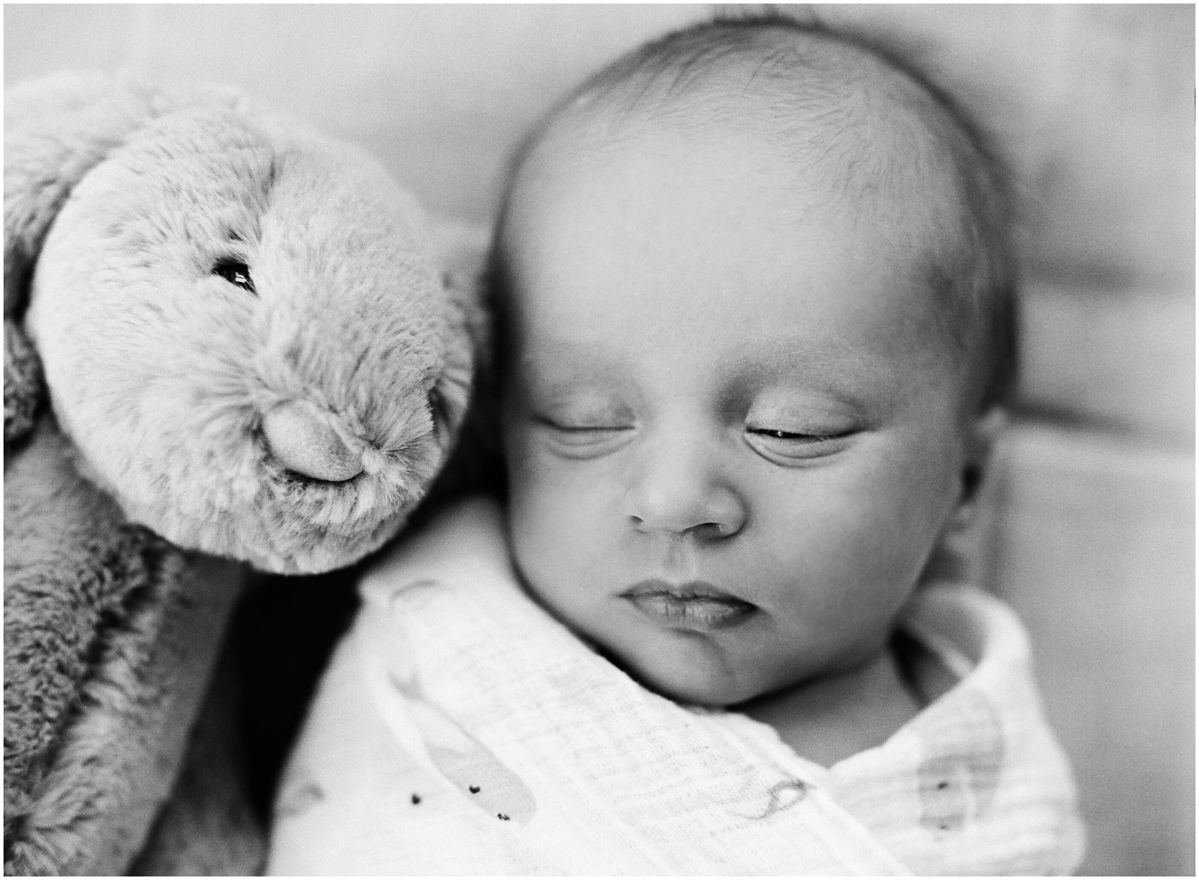 baby opening his one eye and sleeping with toy rabbit