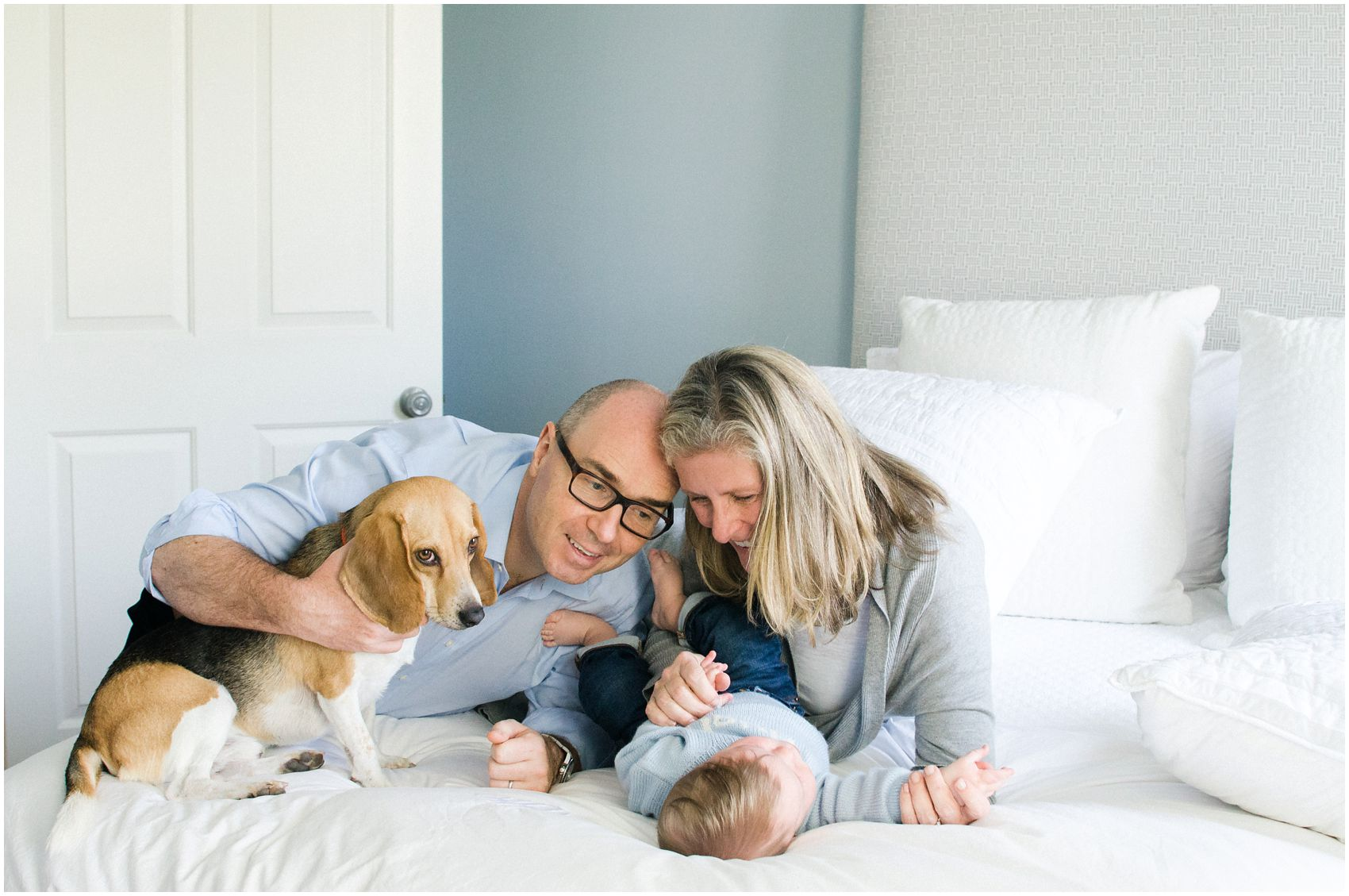 mom and dad in a white bedroom with a family dog and newborn with Miriam Dubinsky Photography