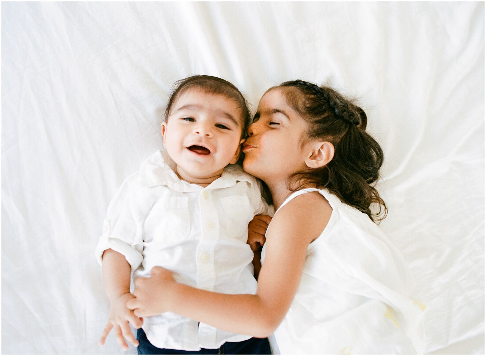 little sister kissing her baby brother laying on a white comforter