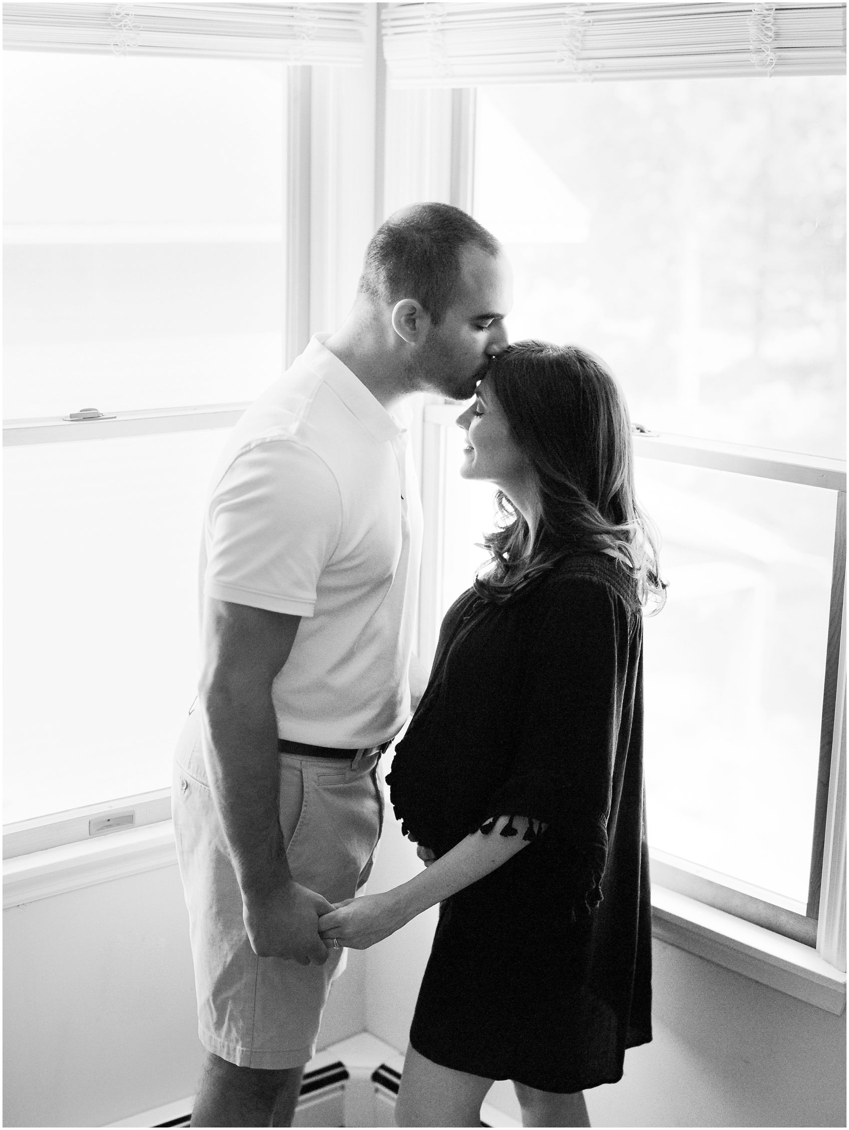 intimate black and white portrait of a pregnant couple at home during maternity photoshoot