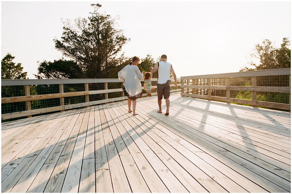 mom and dad jumping on the walkway to the beach during maternity session in Sandy Hook NJ.