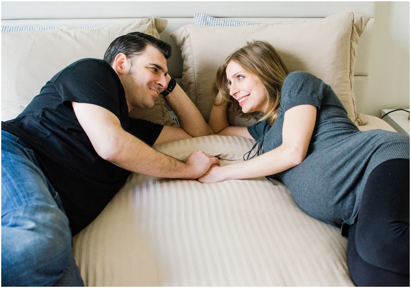 pregnant couple laying in bed and looking at each other