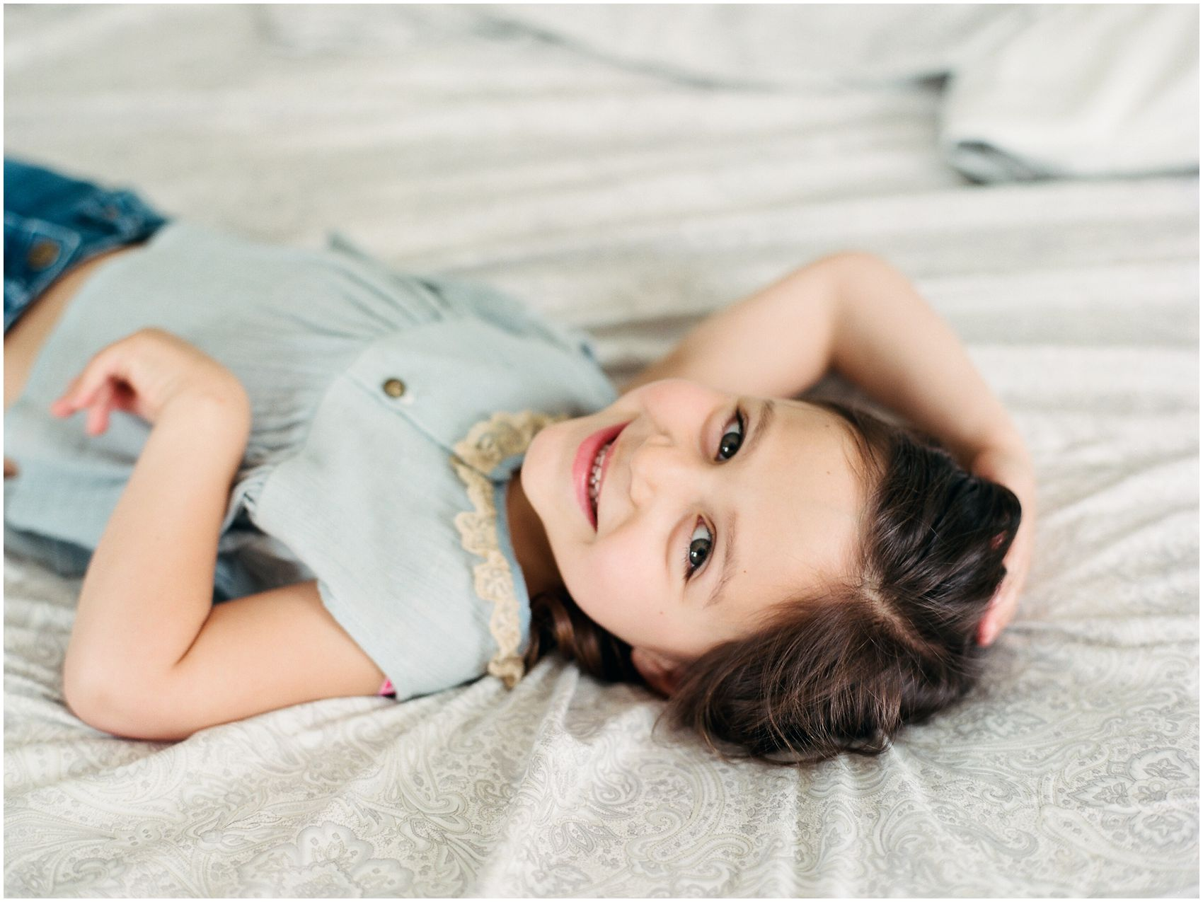 little girl smiling in lifestyle family portraits in bed of her Montclair home